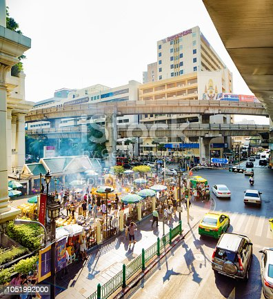 Bangkok Thailand Erawan shrine elevated scene in Pathum Wan commercial area with a small crowd  engaged in rituals. light traffic and a sky train are visible around the shrine.