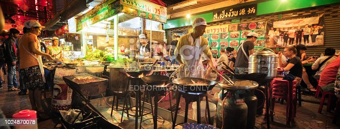Bangkok Thailand night market scene with tourists and restaurateurs panorama. A man is preparing several dishes at once over flames in wok while people eat in the background.