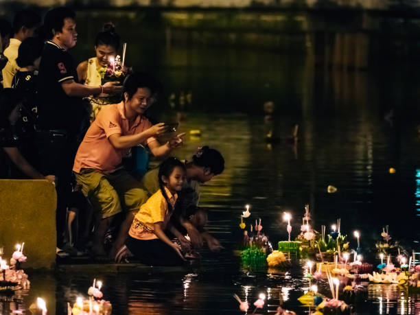 bangkok, thailand on november: family activity with take picture, hold krathong and reflection of fire from candle in the river from loykrathong festival and thailand culture - kratong stock photos and pictures