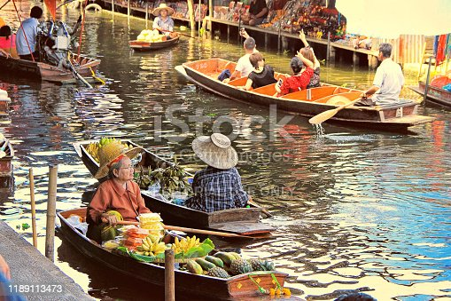 Bangkok, Thailand - May 08, 2018: unidentified tourists and traditional vendors on the famous floating market Damnoen Saduak in Bangkok. It is a traditional market on the khlongs, where they sell goods and food from the boats.