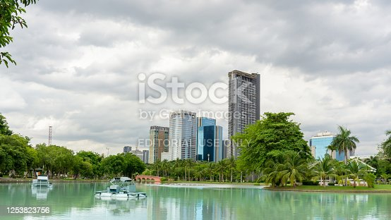 Bangkok, Thailand-July 1, 2020:  Lake and garden view to building under cloudy sky of Chatuchak park, landmark and famous public park in Bangkok for people come to joy and relaxing