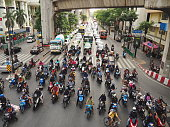 People on motorbikes gathered in front of big lines of vehicles behind them at the red traffic light.