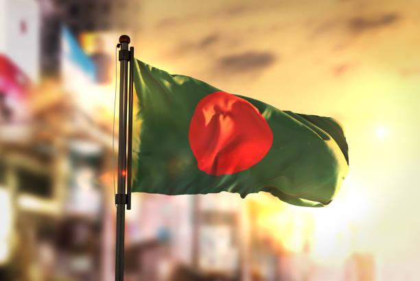 Bangladesh Flag Against City Blurred Background At Sunrise Backlight stock photo