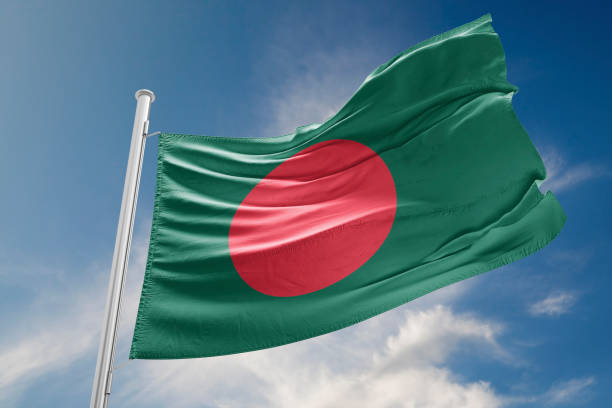 Bangladesh Flag is Waving Against Blue Sky stock photo