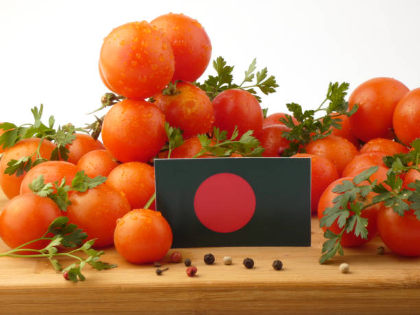 Bangladesh flag on a wooden panel with tomatoes isolated on a white background stock photo