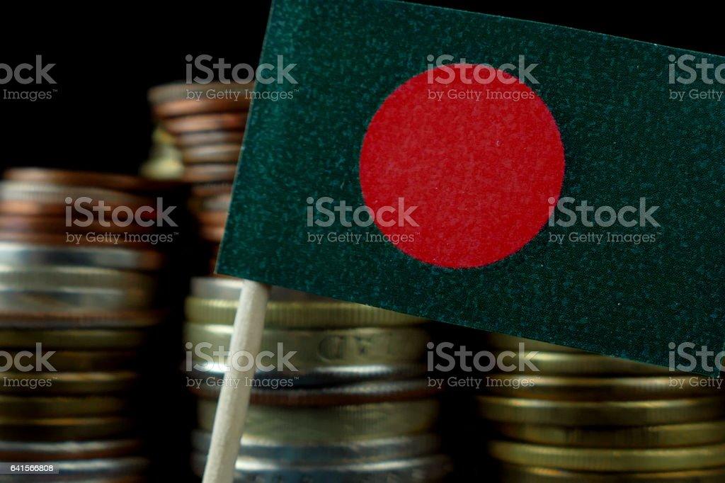 Bandera de Bangladesh ondeando con pila de dinero monedas macro - foto de stock
