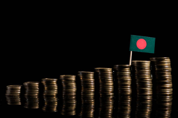 Bangladeshi flag with lot of coins isolated on black background stock photo