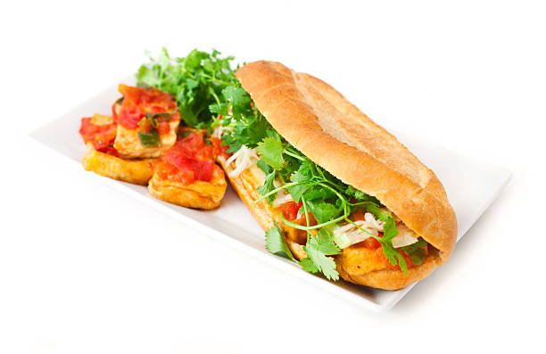 Banh mi tofu Banh mi ¬ vietnamese baguettes sandwiches  on white background. Banh mi - white baguettes prepared with tofu and tomatoes. Decorated with fresh coriander. bánh mì sandwich stock pictures, royalty-free photos & images