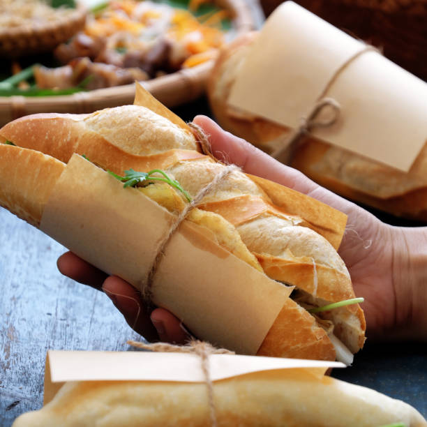 banh mi, Vietnamese bread Woman hand make banh mi thit or Vietnamese bread, famous street food from  raw material: pork, ham, pate, egg and fresh herbs as scallions, coriander, carrot, cucumber, chilli. bánh mì sandwich stock pictures, royalty-free photos & images