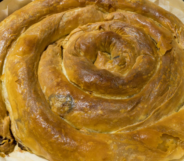 Banitsa (Bulgarian: баница, also transliterated as banitza) is a traditional Bulgarian food prepared by layering a mixture of eggs and cheese between filo pastry and then baking it in an oven. stock photo