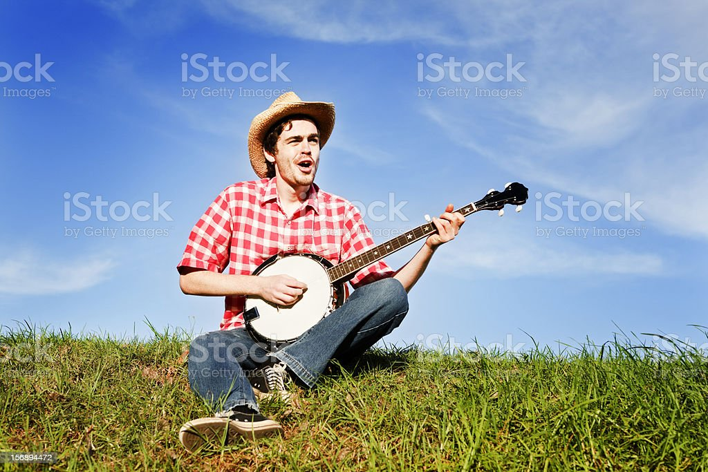 Banjo playing country singer in summertime rural setting stock photo