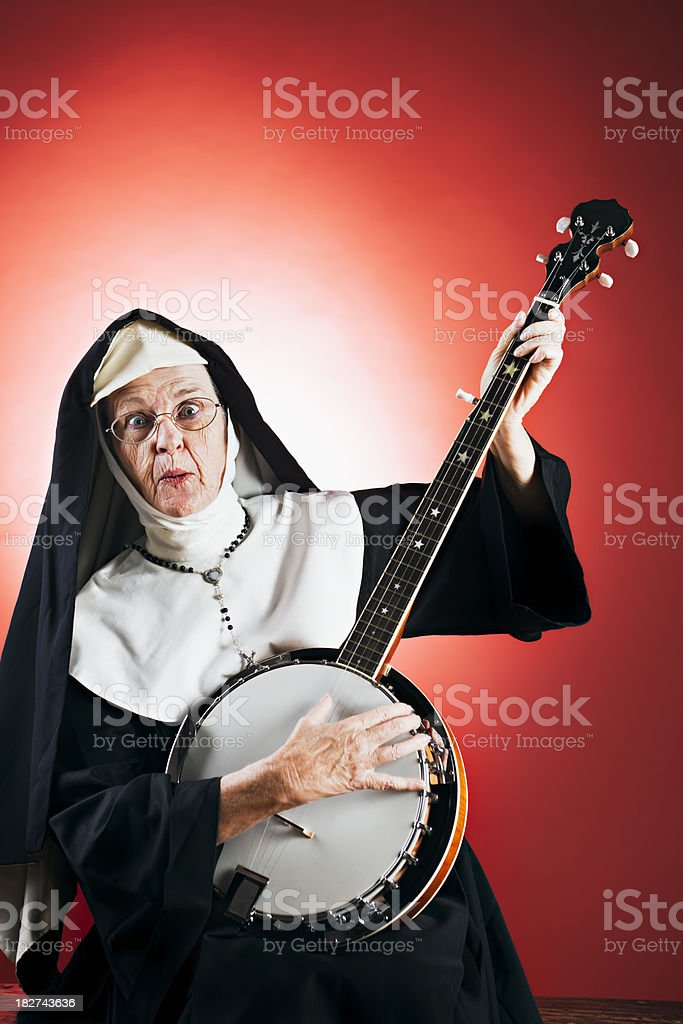 Banjo playing nun strikes final chord. stock photo
