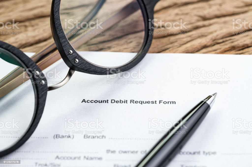 Bank account, debt or financial sign in concept, Account debit request form, paper work document of banking form with pen and eyeglasses on wood table, open an account for savings and investment stock photo