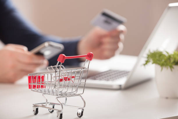 Bank card nearby a laptop and mini shopping cart on white background top view. Online shopping. Bank card nearby a laptop and mini shopping cart on white background top view. home shopping stock pictures, royalty-free photos & images