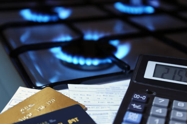 bank cards and a calculator on the background of a gas stove bank cards and a calculator on the background of a burning  gas stove tariff stock pictures, royalty-free photos & images