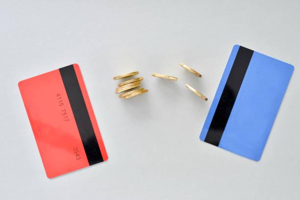 bankkarten sind in den farben der lebende korallen und blau mit glänzenden gelben münzen als symbol für den elektronischen austausch von geld - austauschen stock-fotos und bilder