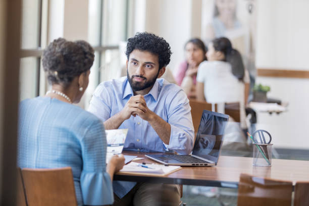 Bank customer considers opening a new account Mature female bank customer discusses opening a savings account with a bank employee. The customer is holding an informational brochure. incidental people stock pictures, royalty-free photos & images