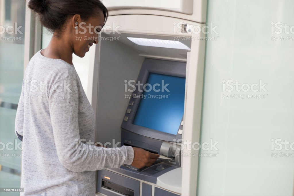 Bank customer woman taking cash money from ATM. stock photo