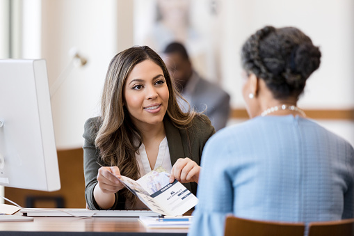 A cheerful female banker explains the different types of banking accounts to a new customer. The banker is showing the customer an informational brochure.