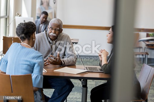 Two female bank employees meet with a senior man to help him plan his investment strategy.