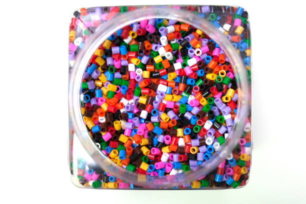 bank filled with colorful pony balls on a white background. stock photo