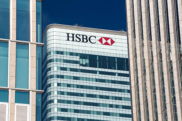HSBC Bank Headquarters London London, United Kingdom - August 28, 2013: The headquarters of HSBC Bank at Canary Wharf in the financial heart of London pictured against a clear blue sky. The building is sandwiched between two other buildings. hsbc stock pictures, royalty-free photos & images