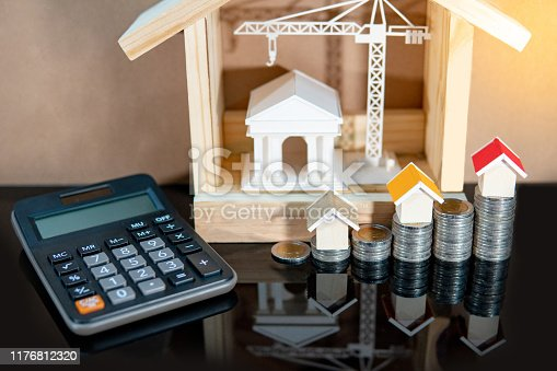 Banking concept. Loan interest rate calculation. Saving money for property investment or real estate development. Home mortgage and lease. Coin stacked, house and bank models with calculator on table.
