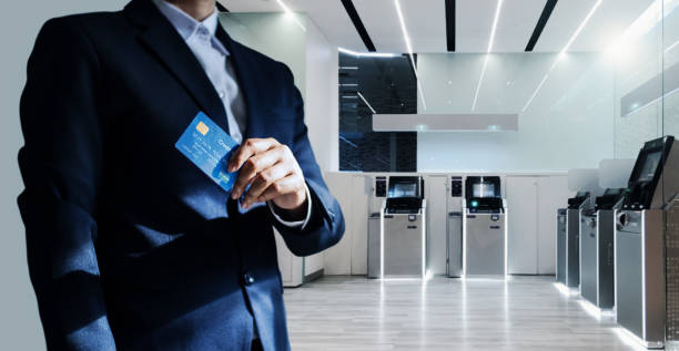 Bank manager and credit card in hand, business man standing confidently with pride in modern financial, futuristic, technology and banking network connection Bank manager and credit card in hand, business man standing confidently with pride in modern financial, futuristic, technology and banking network connection banks and atms stock pictures, royalty-free photos & images