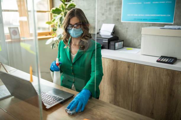 Bankmanager desinfizieren Schreibtisch im Büro – Foto