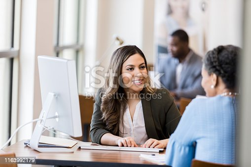 As she types in the information needed to open a new account, the bank manager smiles at the mature adult customer.