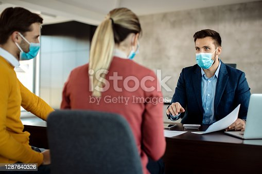 Financial consultant communicating with a couple and wearing face mask during the meeting due to coronavirus pandemic.