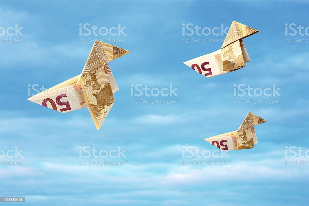 Bank note paper birds flying away on blue sky royalty-free stock photo