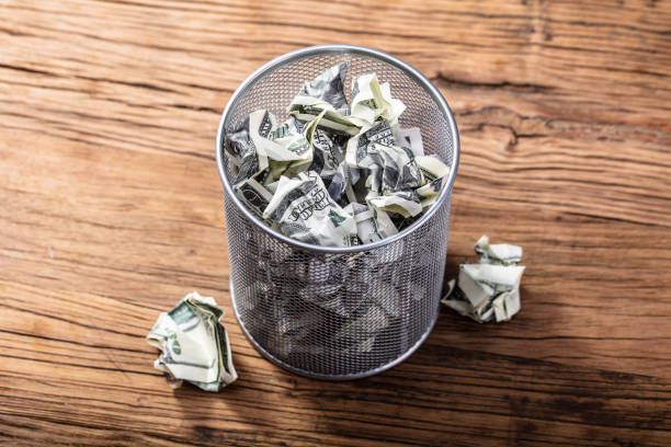 bank notes in dustbin - throw money away stock pictures, royalty-free photos & images