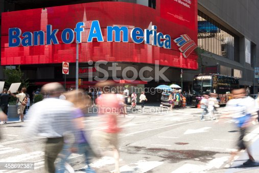 Manhattan, New York USA - July 9, 2011: People and tourist walking by the colorful electronic sign of Bank of America. The sign is one of many colorful signs in Times Square.