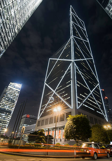 Bank of China at night Taxis passing the illuminated Bank of China tower at night in Hong Kong. bank of china stock pictures, royalty-free photos & images