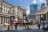 London, UK - June 30, 2014: Bank of England and square in front of bank with roads and red busses.