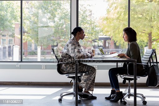 Attentive female soldier meets with a bank manager or loan officer about obtaining a loan.