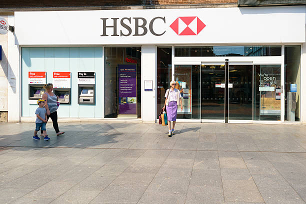 HSBC bank on High Street Exeter, Devon, United Kingdom - August 23, 2016: Customer came out of HSBC branch on High Street. HSBC claims it saved customers £100m in fees since it launched it's overdraft text alert in 2014. hsbc stock pictures, royalty-free photos & images