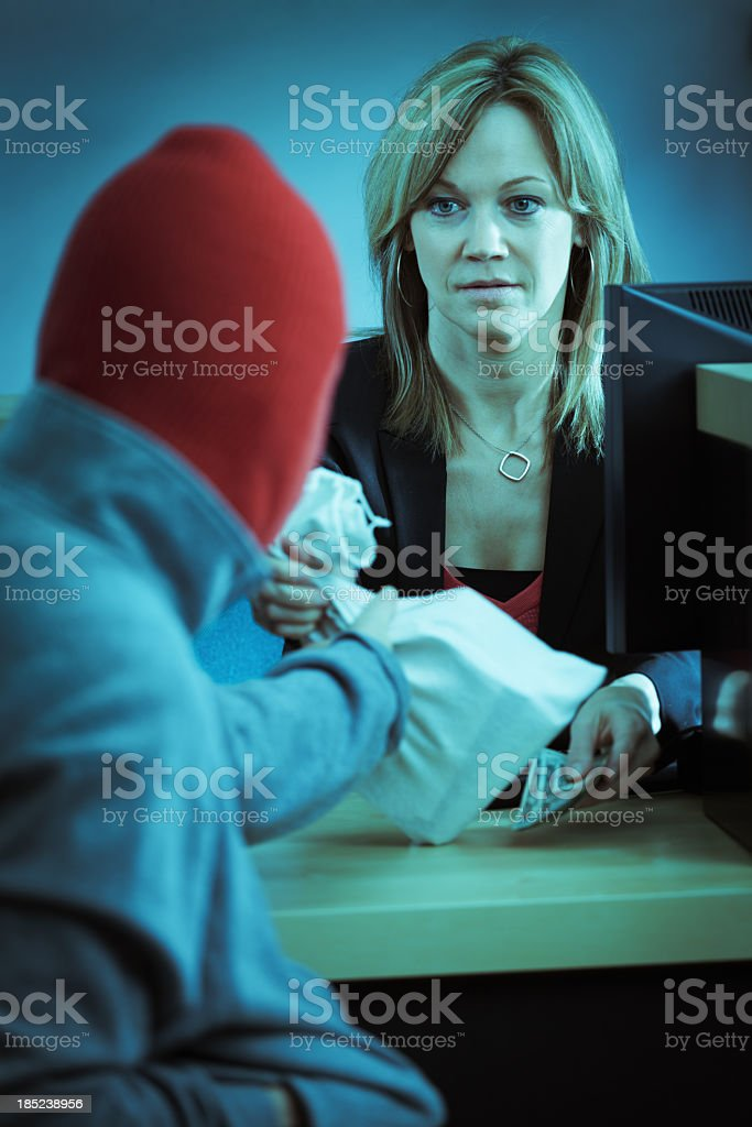 Bank Robber in Action Robbing Retail Banking Counter stock photo