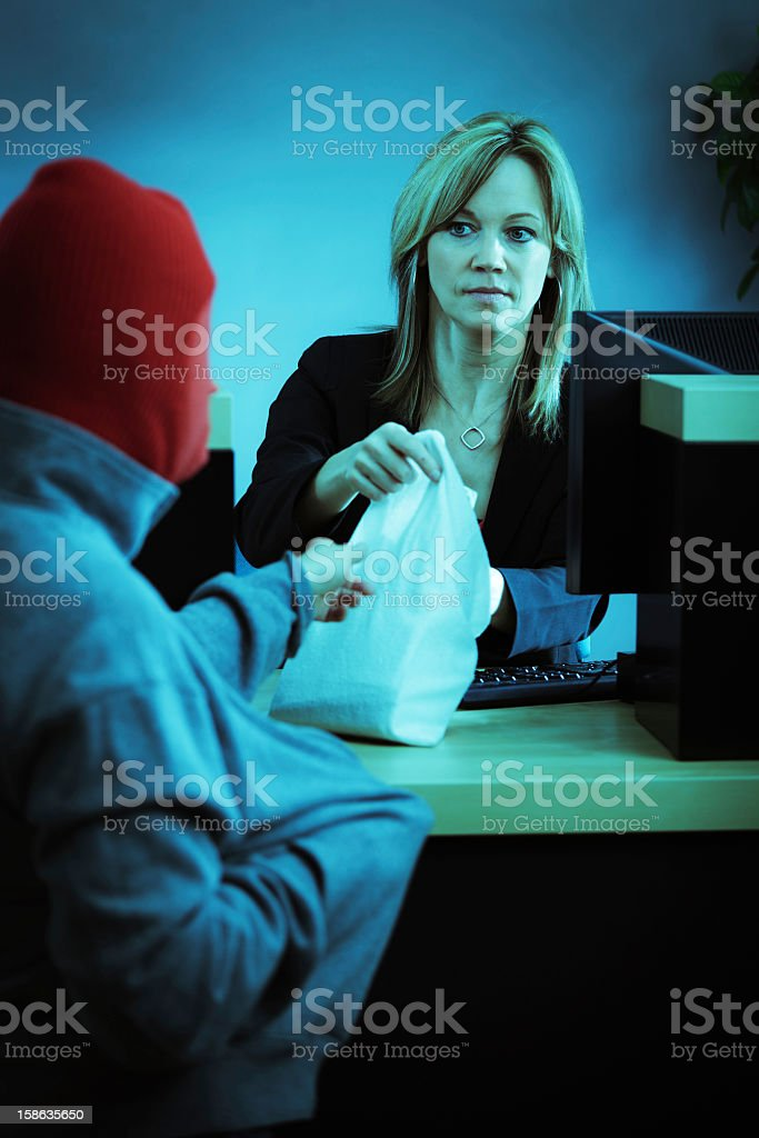 Bank Robber in Action Robbing Retail Banking Teller Counter stock photo