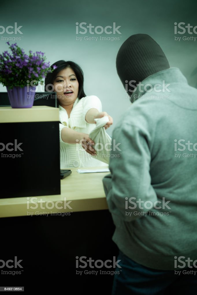 Bank Robbery in Progress with Asian Bank Teller at Retail Bank Counter stock photo