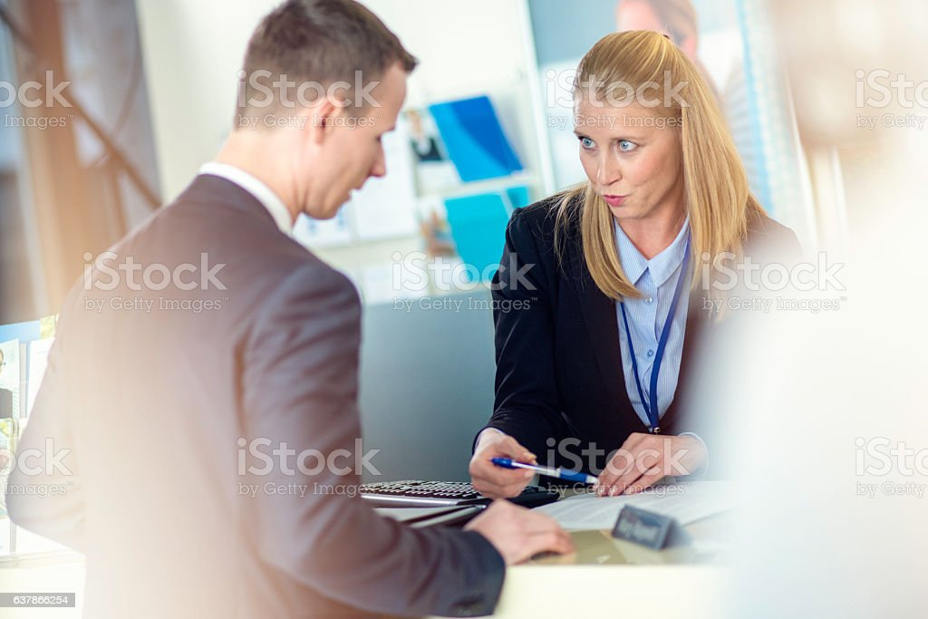 Bank teller explaining financial contract to businessman stock photo