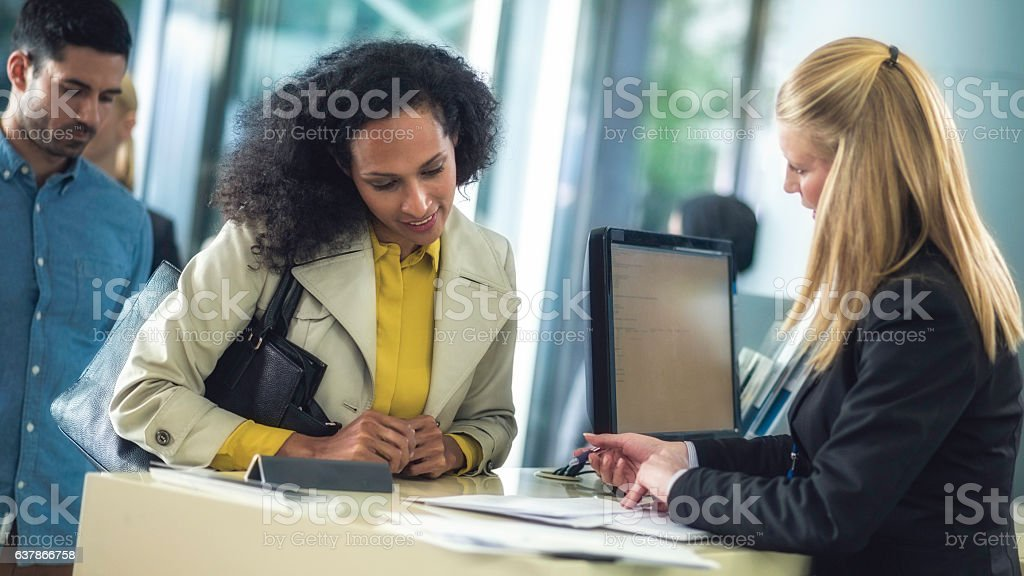 Bank teller explaining loan details to customer - foto de acervo