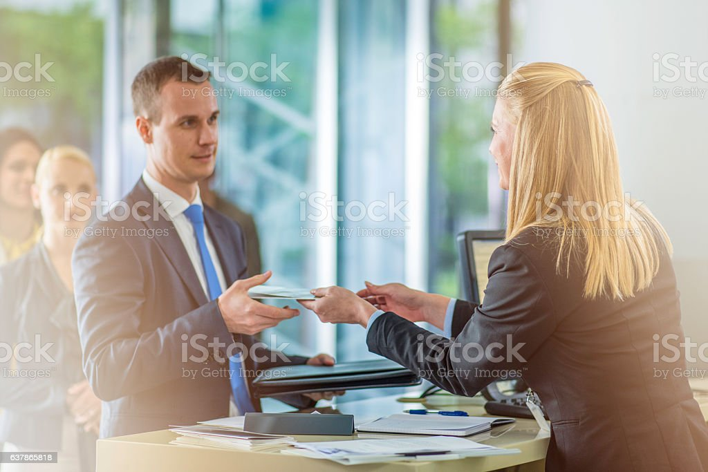 Bank teller giving document to a customer stock photo