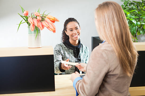 Bank Teller Helping Customer in Retail Banking Window Counter stock photo