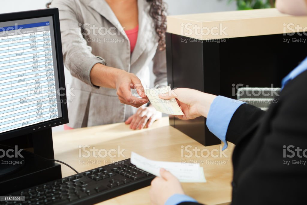 Bank Teller Service with Customer Deposit Transaction Over Business Counter stock photo