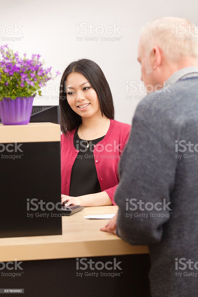 An adult man bank customer making a financial transaction with a bank...