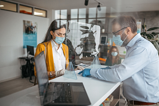 Bank teller discussing paperwork with customer at bank counter wearing protective gloves and face mask. Office with acrylic glass partition on desk. Acrylic glass wall - protection against coughs and spitting, protection against viruses.