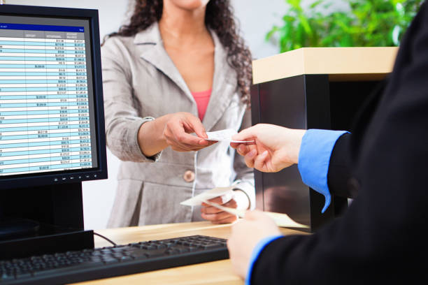 Bank Teller Working with Customer at Bank Counter in Retail Bank stock photo