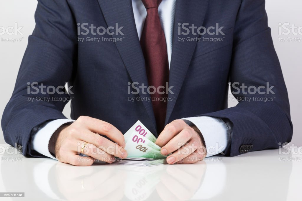 bank teller's hands counting euro banknotes on the table. stock photo